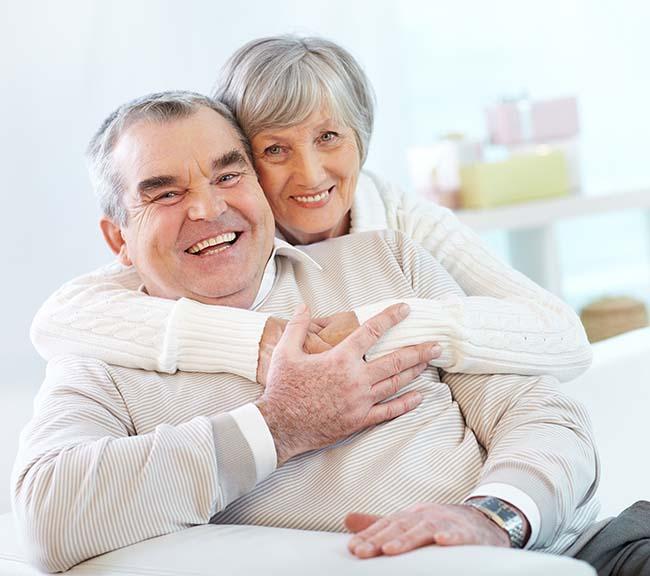 couple senior heureux assis dans canapé