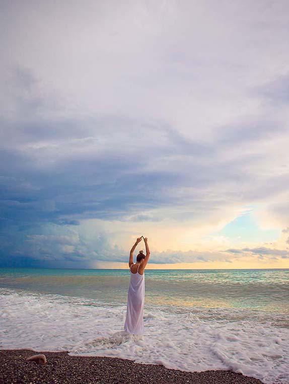 Femme qui s'étire au bord de la plage