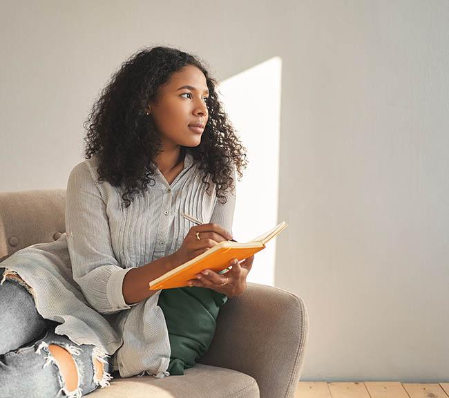 Jeune femme afro assise dans son canapé